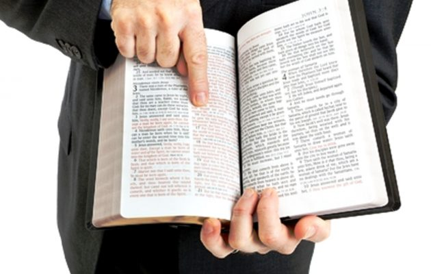 Businessman or minister holding a bible open to John 3:16.  White background.